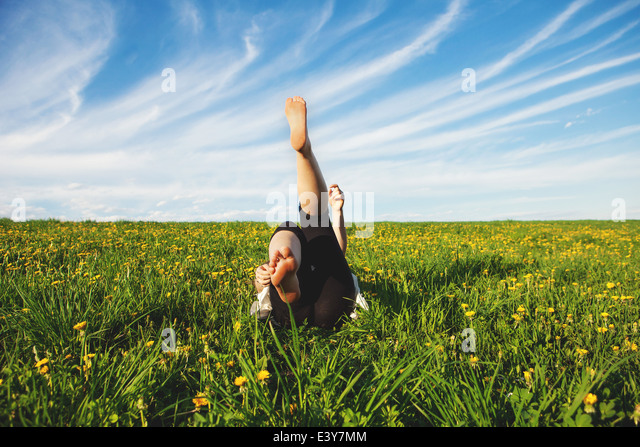 Young woman lying on grass with legs raised - Stock Image