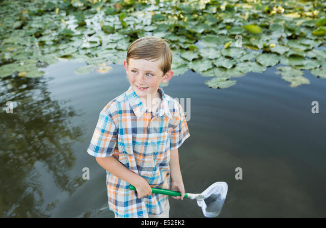 A young boy standing in shallow water with a fishing net. - Stock Image