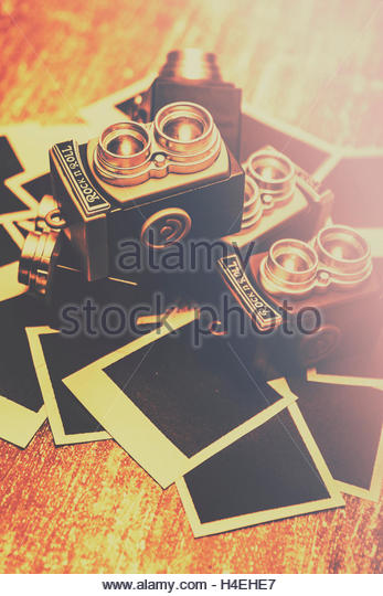 Retro twin lens reflex camera toys laying in a creative still life on instant blank photos. Photography symbols - Stock Image