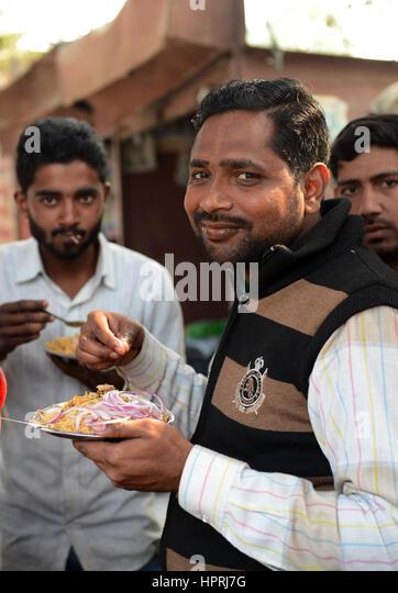 Indian men enjoying Chicken Biryani in the streets of Kannauj, Uttar Pradesh. - Stock Image
