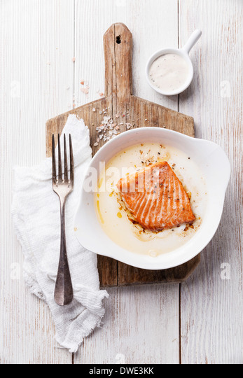 Baked salmon in a bowl on a wooden board - Stock-Bilder