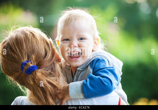 Mother holding happy screaming boy - Stock Image