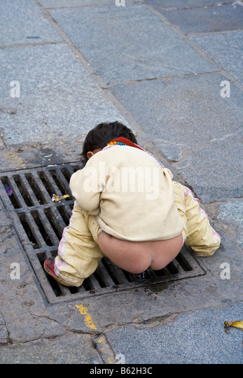 Young Tibetan child using 'public toilet' in the Barkhor, Lhasa, Tibet. JMH3706 - Stock Image