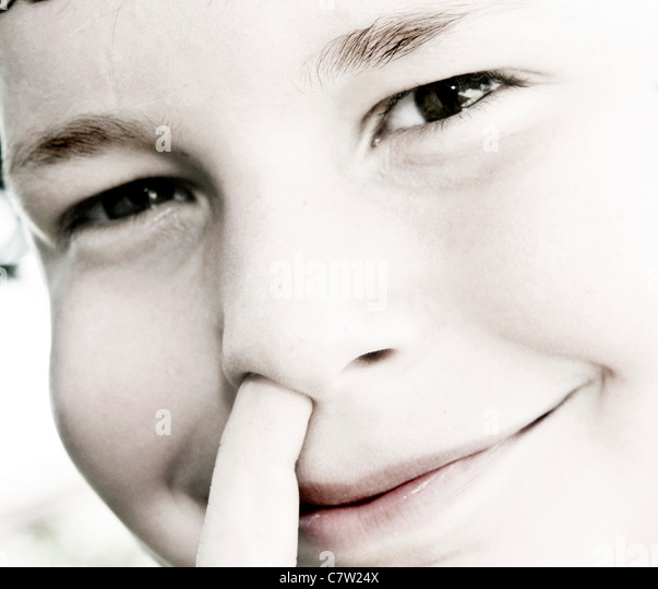 Close-up of a boy picking his nose - Stock Image