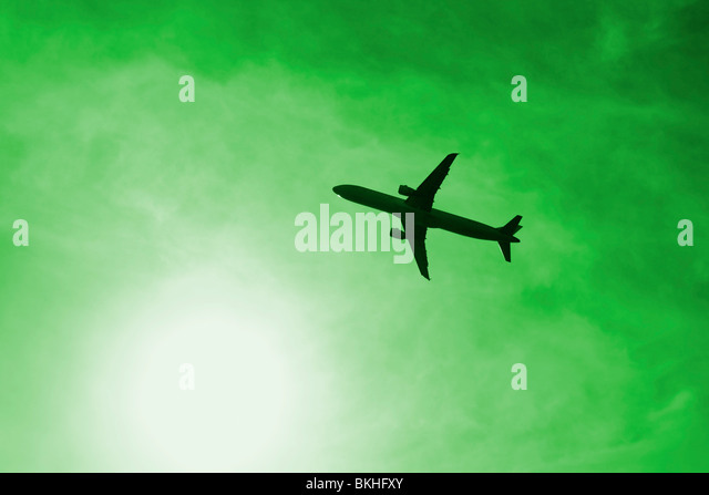 Plane near sun against green sky. Could be used to depict pollution, air travel, carbon footprint... - Stock-Bilder