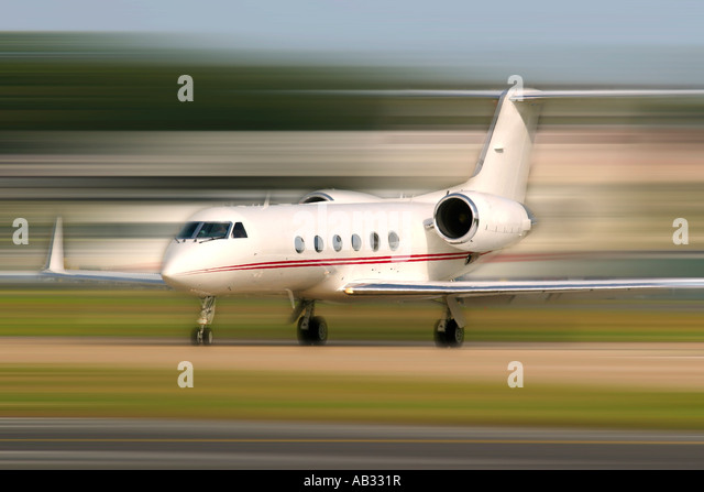 Corporate jet prepareing for departure at an airport with motion blur in the background - Stock Image