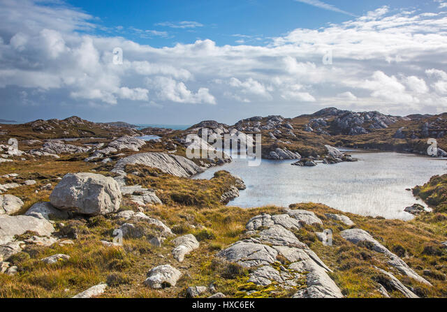 Sunny clouds over craggy rocks and water, Golden Road, Harris, Outer Hebrides - Stock Image