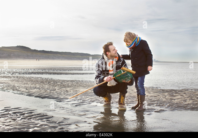 Mid adult man and son with fishing net on beach, Bloemendaal aan Zee, Netherlands - Stock Image