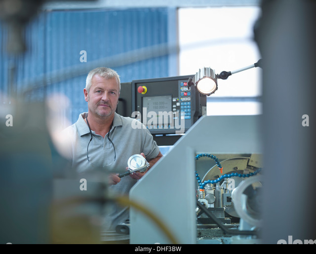 Lathe operator working in factory, portrait - Stock Image