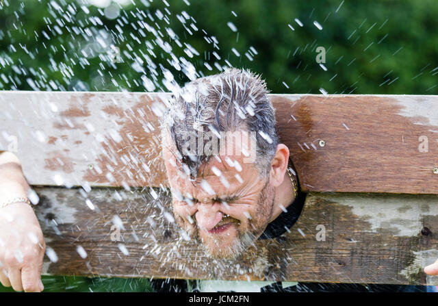England, Coxheath. World custard pie championships. Man in stocks, getting hit by wet sponge. Blurred motion. - Stock Image