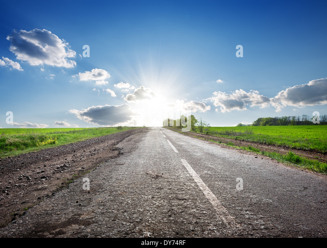 Asphalted highway in the field and sunlight - Stock Image