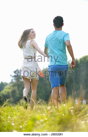 Rear View Of Couple Running Through Field In Countryside - Stock-Bilder