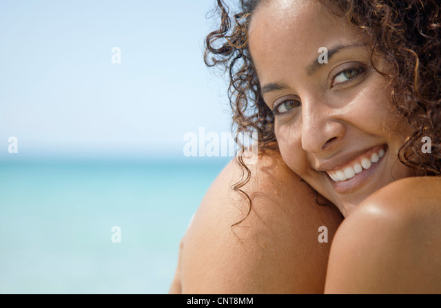 Woman at the beach, smiling, portrait - Stock Image