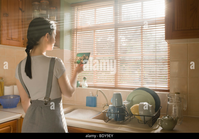 Woman reading post card - Stock Image