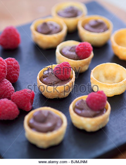 Several pastry shells filled with chocolate mousse & raspberries - Stock Image