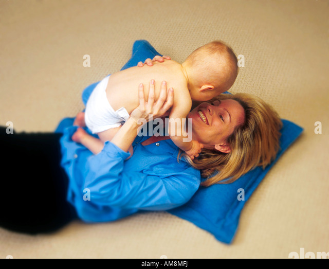 A smiling infant and mother at play - Stock Image