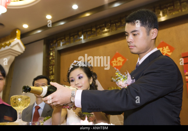 Bride and groom pouring champagne together at reception - Stock Image
