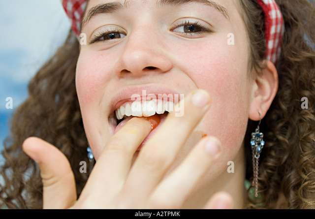 Girl eating tomato sauce - Stock Image