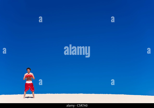 Boxer stands on sand dune gloves connected ready for action. - Stock-Bilder