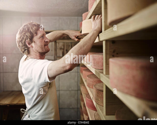 Dairyman storing his mountain cheese, Steinbergalm, Inneralpbach, Alpbach, Tyrol, Austria - Stock-Bilder