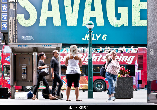 onlooker pauses to survey kinetic flurry of movement & bold advertising for current movie on Broadway in midtown - Stock Image