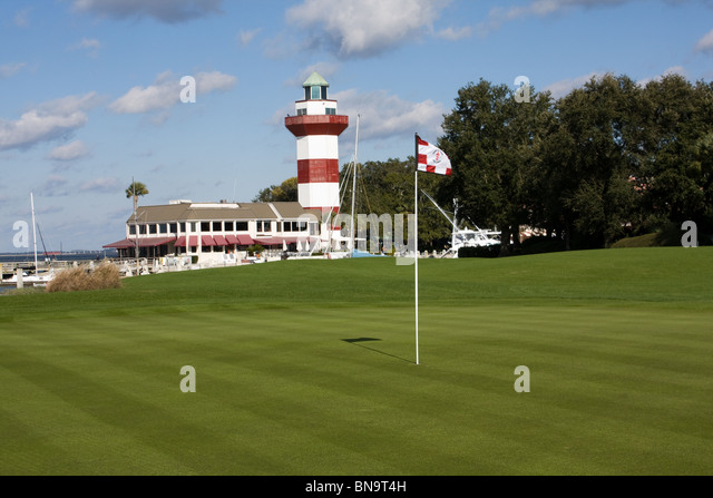 The famous Hilton Head Lighthouse stands behind the 18th green of the Harbortown Golf course in Hilton Head, SC - Stock-Bilder