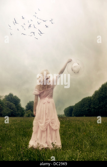 a girl with a pink dress on a meadow, waving to birds with a sunhat - Stock Image