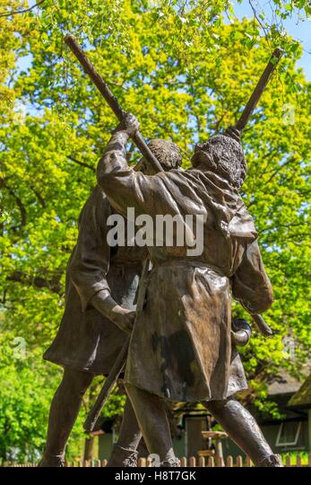 A sculpture of medieval fighting men using poles - Stock Image