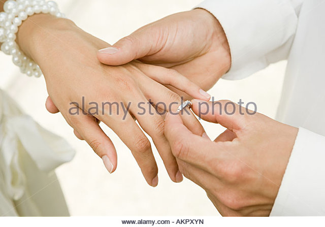 Man placing wedding ring on brides finger - Stock-Bilder