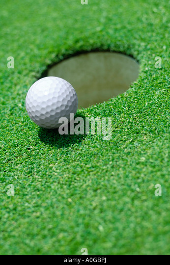 Golf ball on edge of hole on golf green - Stock Image