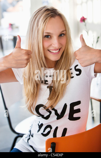 Portrait of a beautiful woman showing thumbs up at a cafe - Stock Image