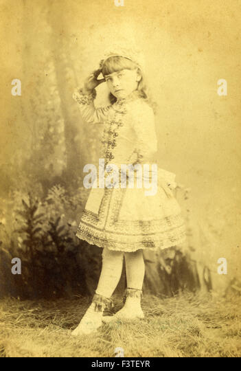 Girl standing in a dress and stockings during a photo sitting that produced a tin-type photograph during the late - Stock-Bilder
