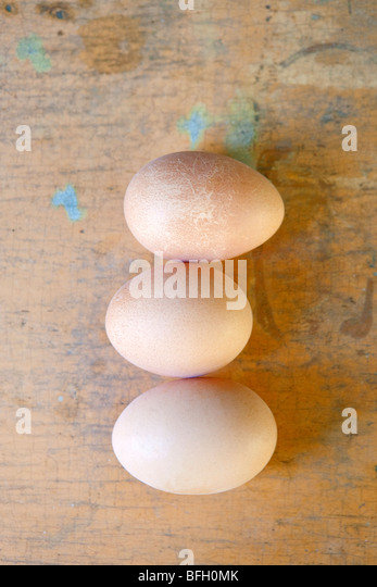 three brown hen eggs on rustic surface - Stock Image