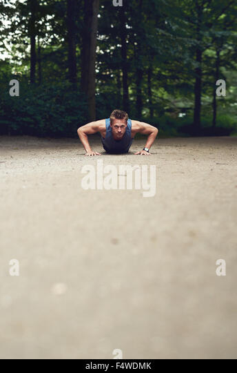 Low angle view of a fit young man doing press-ups in a park as part of his daily exercise regime, with foreground - Stock Image