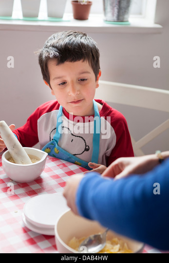 Child helps to bake a cake - Stock Image