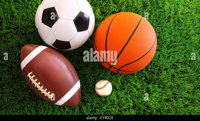 Assortment of sport balls on green grass - Stock Image