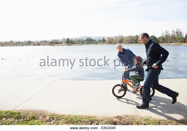 Male couple running next to son on bicycle in park - Stock Image