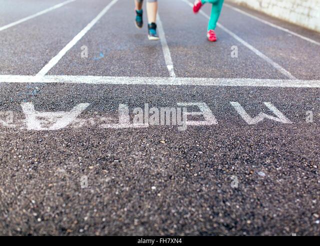 Legs of two running girls on tarmac - Stock Image