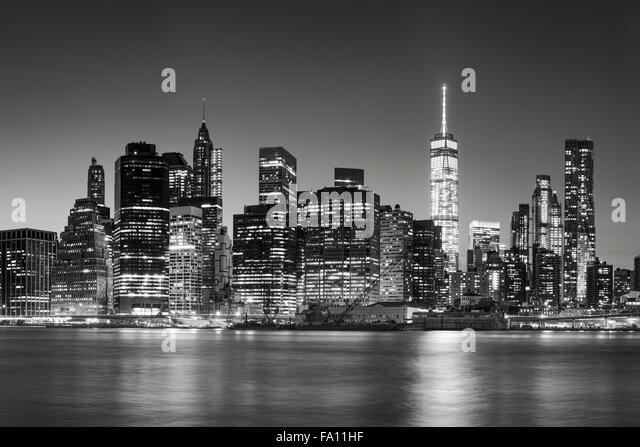 Black & White East River view of Financial District skyscrapers at dusk. Illuminated Lower Manhattan skyline, - Stock Image