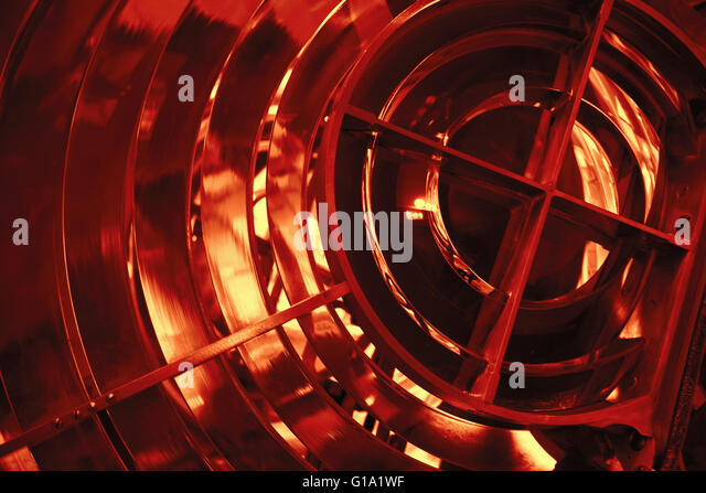 Lighthouse lamp with lens made of glass rings. Closeup photo with selective focus and red tonal correction filter - Stock Image