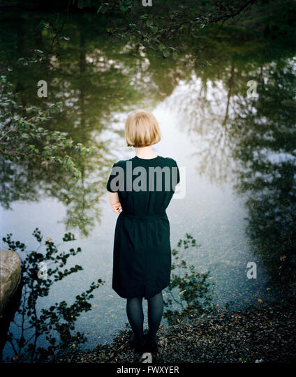 Finland, Varsinais-Suomi, Young woman standing at edge of lake - Stock Image