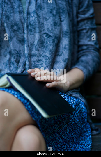 Woman sitting with open book resting on lap, cropped - Stock Image