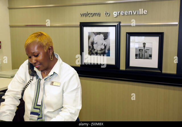 Alabama Greenville Hampton Inn motel lodging Black woman reservation reception check in desk employee job - Stock Image