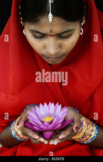 Indian woman offering a Nymphaea Tropical waterlily flower in a red sari - Stock-Bilder