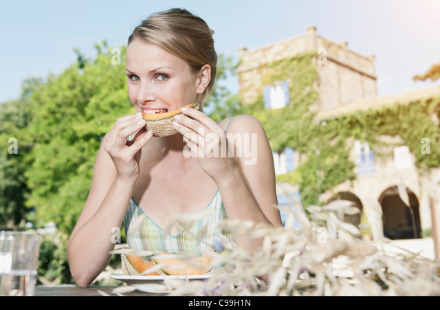 Italy, Tuscany, Magliano, Young woman eating honey melon, portrait - Stock Image
