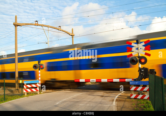 Dutch yellow and blue intercity high speed train passing a railway crossing with the barrier down and flashing warning - Stock-Bilder
