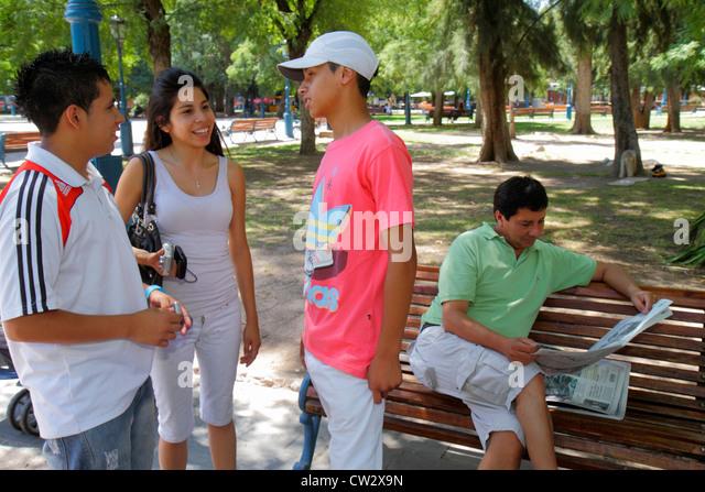 Mendoza Argentina Plaza Independencia public park Hispanic man woman boy teen talking socializing reading newspaper - Stock Image