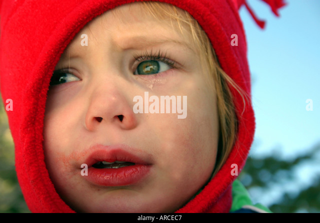child crying with red hat winter - Stock Image