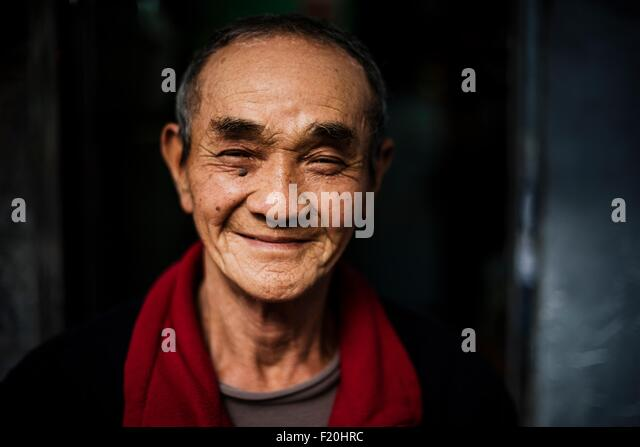 Portrait of senior man wearing red scarf around neck looking at camera smiling - Stock Image