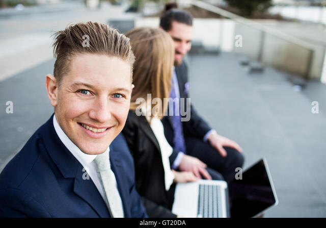Portrait of smiling businessman sitting with colleagues using laptop - Stock-Bilder